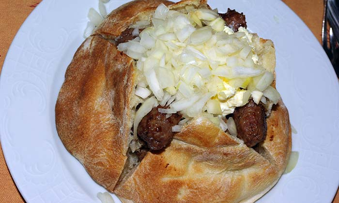 A plate of cevapi in bread with onions
