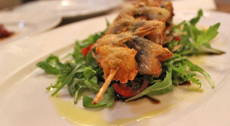 Fried sardines serves on a bed of rocket salad