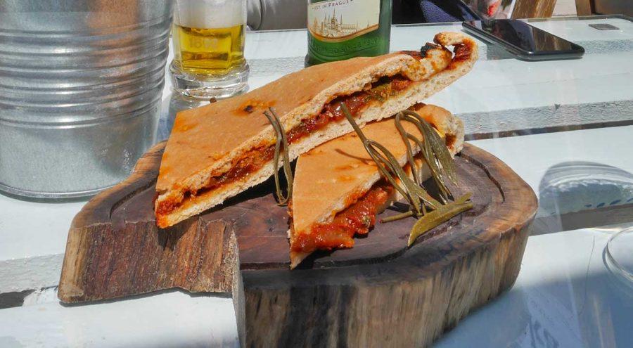 Croatian streetfood, Komiska pogaca, a fisherman's pie filled with tomatoes, anchovies, and onions